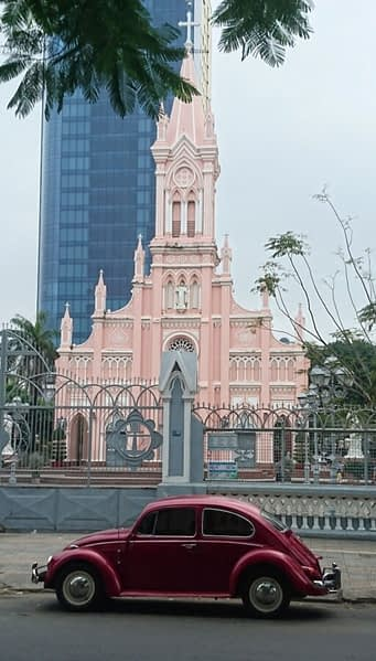 A mixture of cultures and decades with the pastel pink Catholic church in central Da Nang, built in 1923, backed very a modern skyscraper with a 1967 VW Beetle wearing the So-Cal look parked in front