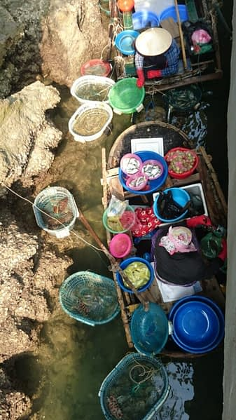 A local fisher selling their wears (look closely, you'll spot them) from under the dock at Bo Hon island