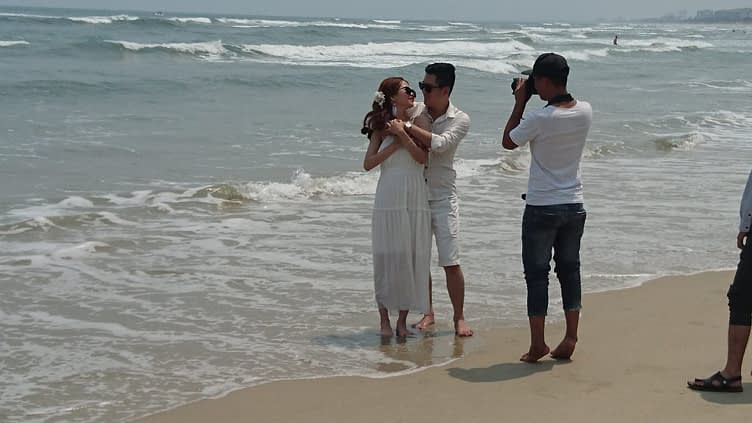 The only thing that litters My Khe beach is newlyweds – every ten metres there's another young couple shooting their wedding photos